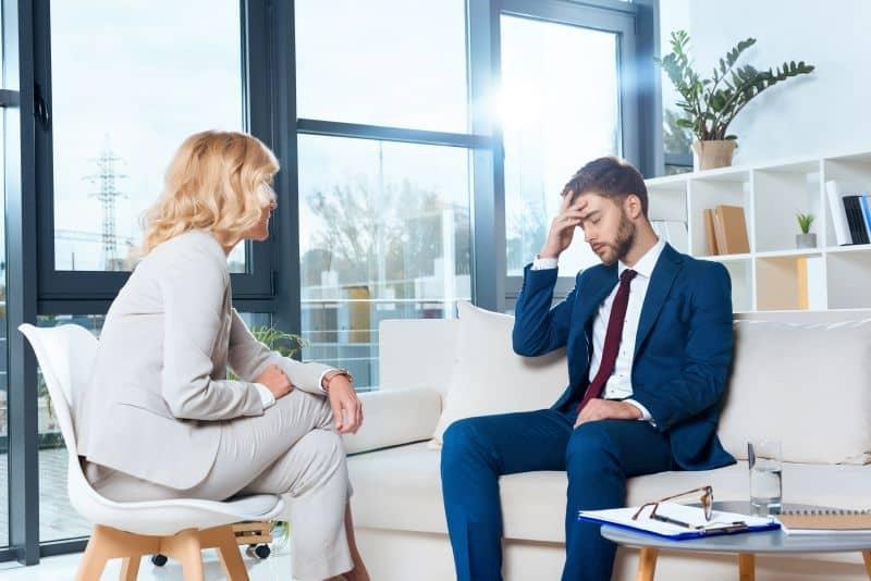 un paziente afflitto parla con la psicologa durante una consulenza psicologica